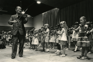 Shinichi Suzuki leads a violin group class of children in the United States (date unknown)